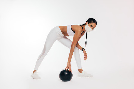 Young woman in sportswear with protective face mask exercising with medicine ball against a white background