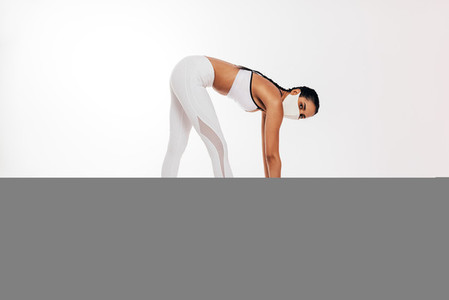 Slim female in sportswear with face mask stretching her body against a white background