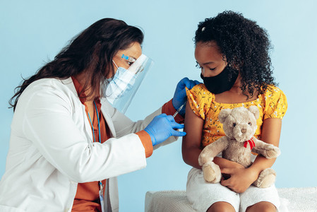Doctor vaccinating girl