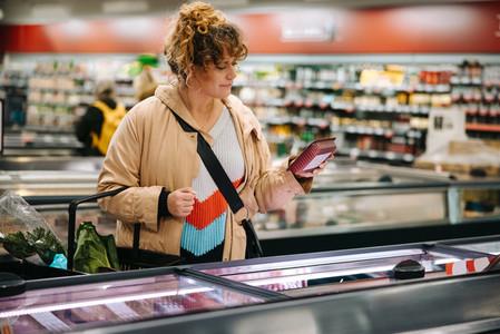 Shopper reading food item labels