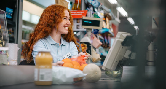 Young cashier attending customer at supermarket