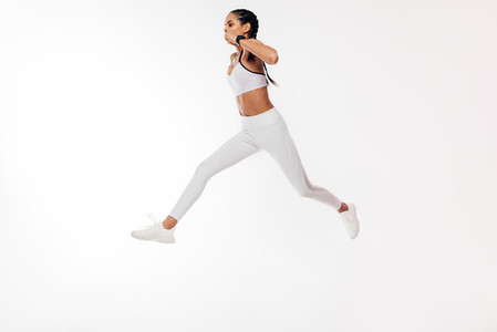 Woman athlete jumping on a white