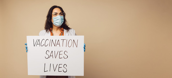 Doctor showing Vaccination Saves Lives signboard