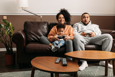 Happy parents with son playing video game Family of three spending time together on couch at home