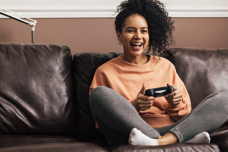 Happy young woman holding a game controller sitting on sofa at home