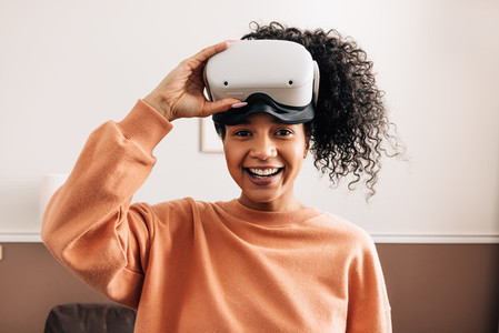 Portrait of mixed race woman holding a VR glasses looking at camera