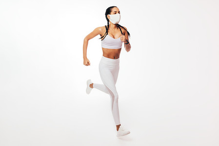 Young fit woman in face mask running on white background in studio