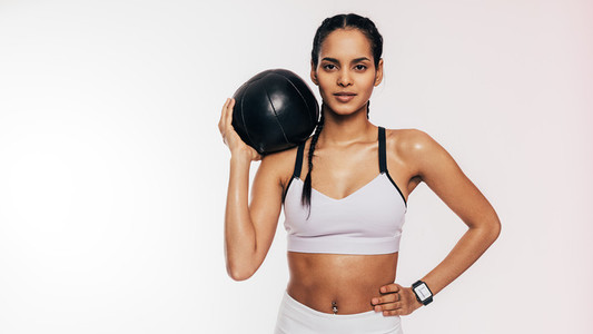 Mixed race woman holding a medicine ball on her shoulder looking at camera