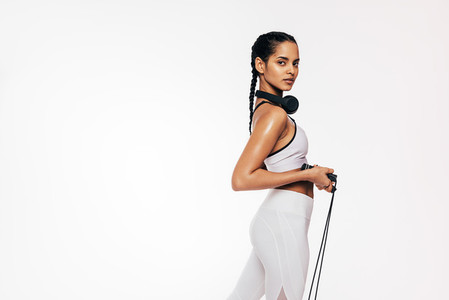 Fitness woman standing with a skipping rope looking at camera