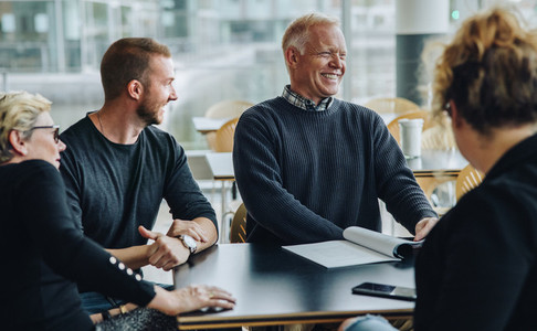 Smiling senior businessman having meeting with team