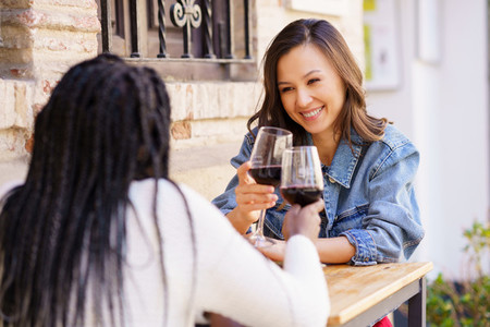 Two women making a toast with red wine sitting at a table outside a bar