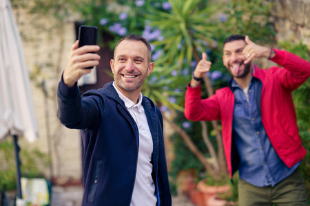 Gay couple making a fun selfie with their smartphone outdoor