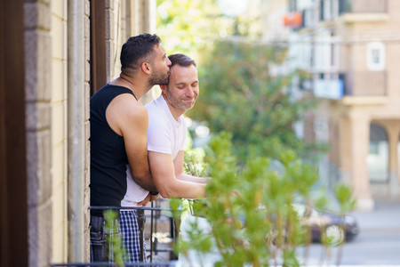 Gay couple in a romantic moment leaning out of their balcony