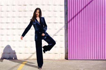 Woman wearing blue suit posing near pink shutter