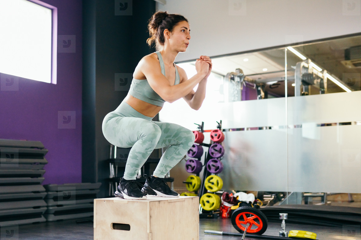 Caucasian female doing box jump workout at gym