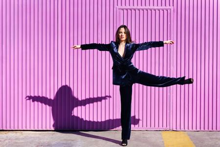 Woman wearing blue suit dancing near pink shutter