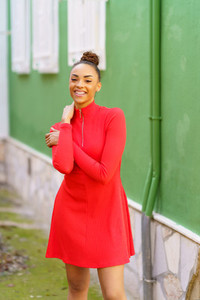 Happy black woman in red dress in front of a green wall
