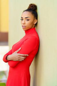 Young mixed woman in red dress with a serious expression in urban background