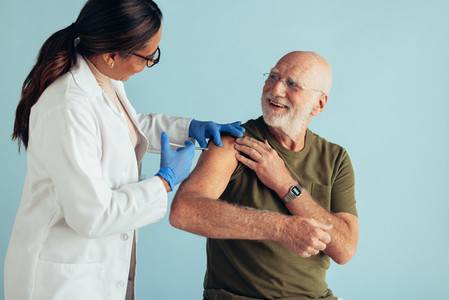 Doctor giving vaccination to elderly man