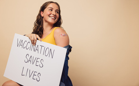 Cheerful woman with a signboard of vaccination saves lives