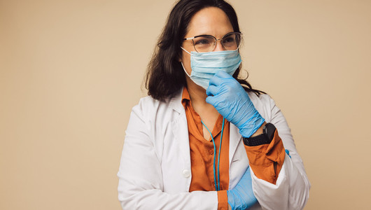 Female doctor with sterile mask on face and gloves