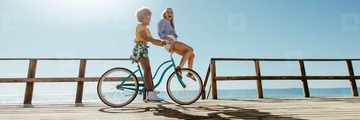 Panorama of joyful friends enjoying riding bicycle together