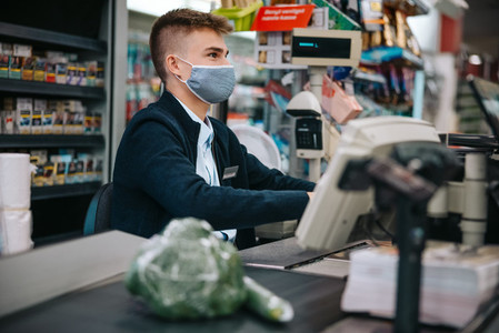 Male cashier at supermarket with face mask