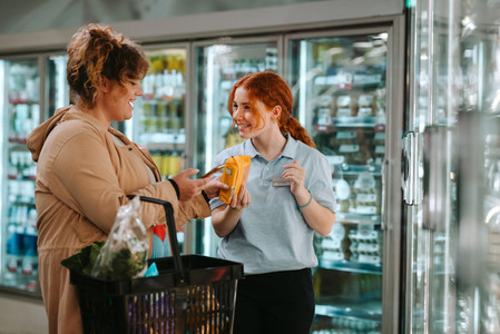Assistant helping customer at supermarket