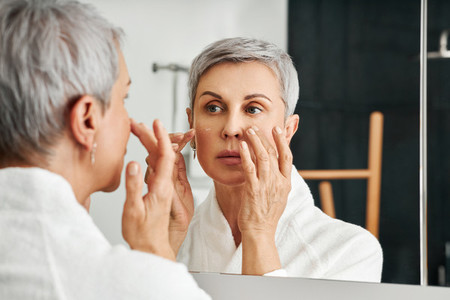 Mature woman applying moisturizer in bathroom  Senior female in bathrobe doing skincare routine