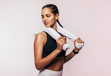 Portrait of a sportswoman with braids holding a white towel looking away