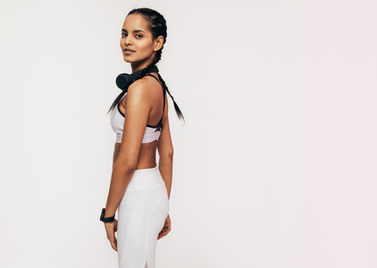 Beautiful mixed race woman in sportswear looking at the camera in a studio