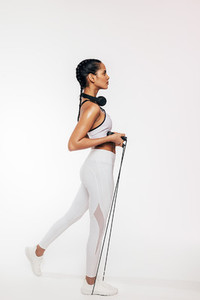 Side view of slim woman exercising with skipping rope over white background