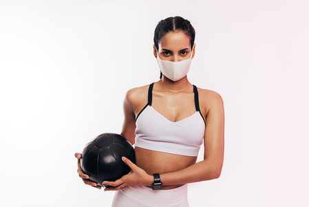 Fitness woman wearing face mask exercising with a medicine ball