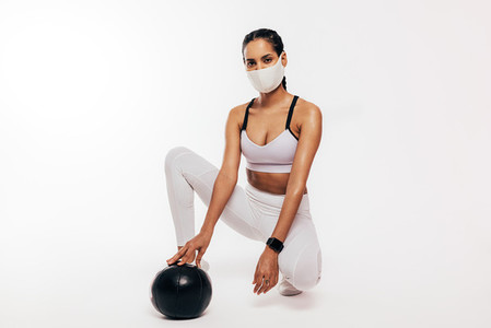 Fitness woman in face mask relaxing after workout with madicine ball