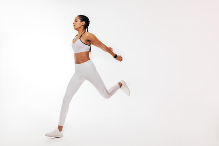 Young mixed race woman running over white background in studio