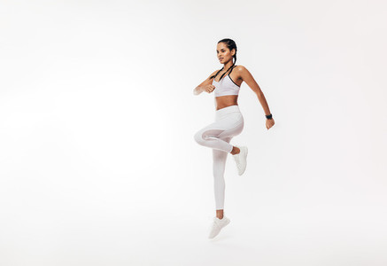 Young fit woman exercising over white background  Female in white sportswear jumping indoors