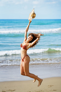 Young woman with beautiful body in swimwear jumping on a tropical beach