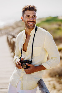 Smiling man photographing in a coastal area