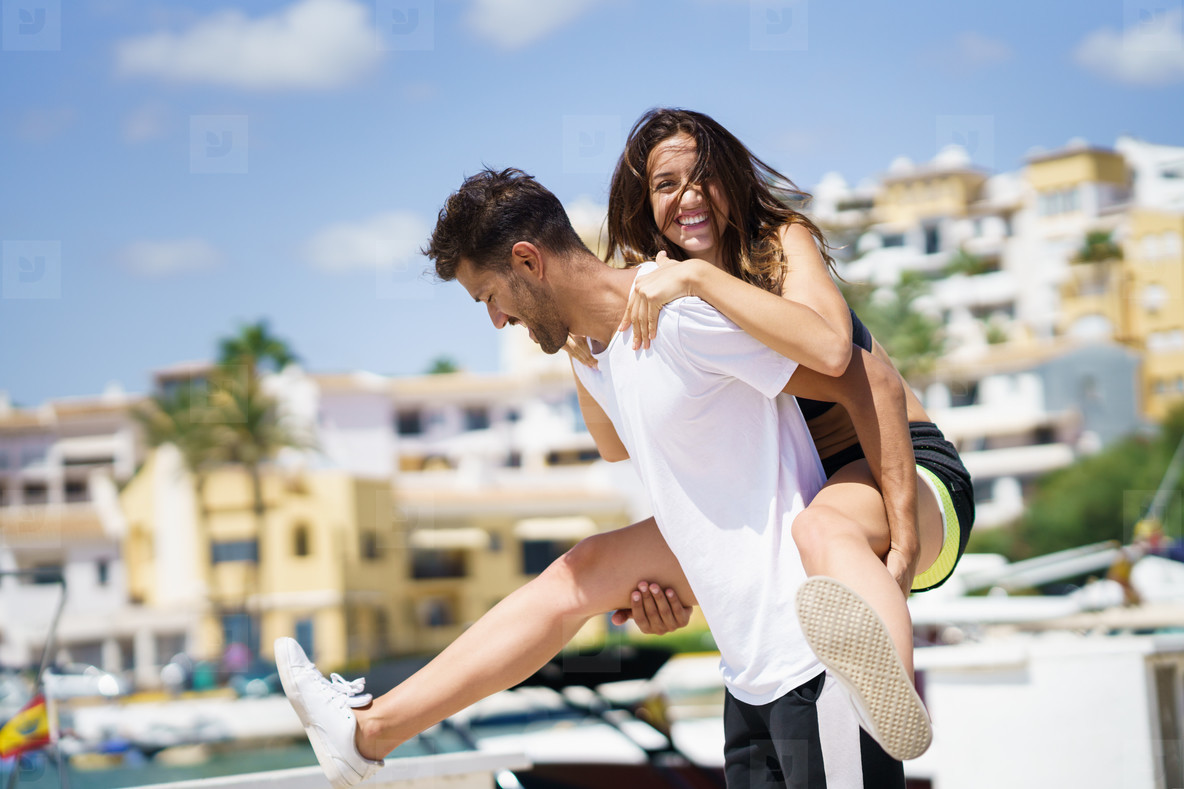 Man carrying his girlfriend on piggyback wearing sport clothes