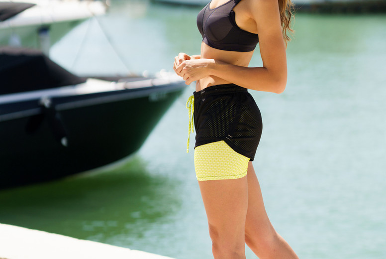 Fitness woman in sportswear outfit training on waterfront harbour