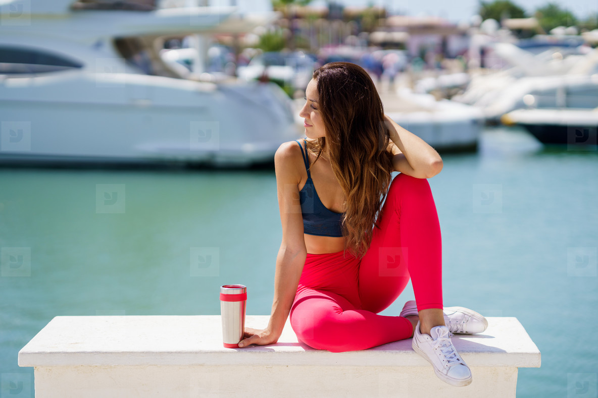 Fitness girl in sportswear outfit training resting to hydrate after exercise