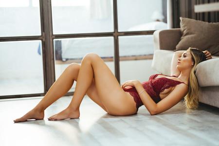 Caucasian girl in red lingerie lying on the floor