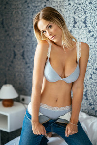 Blonde girl posing in blue bra and jeans