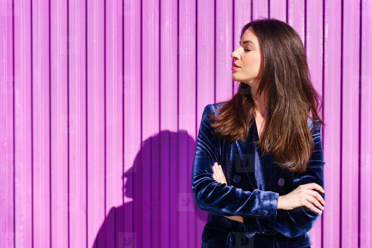 Woman wearing blue suit posing near pink shutter with eyes closed
