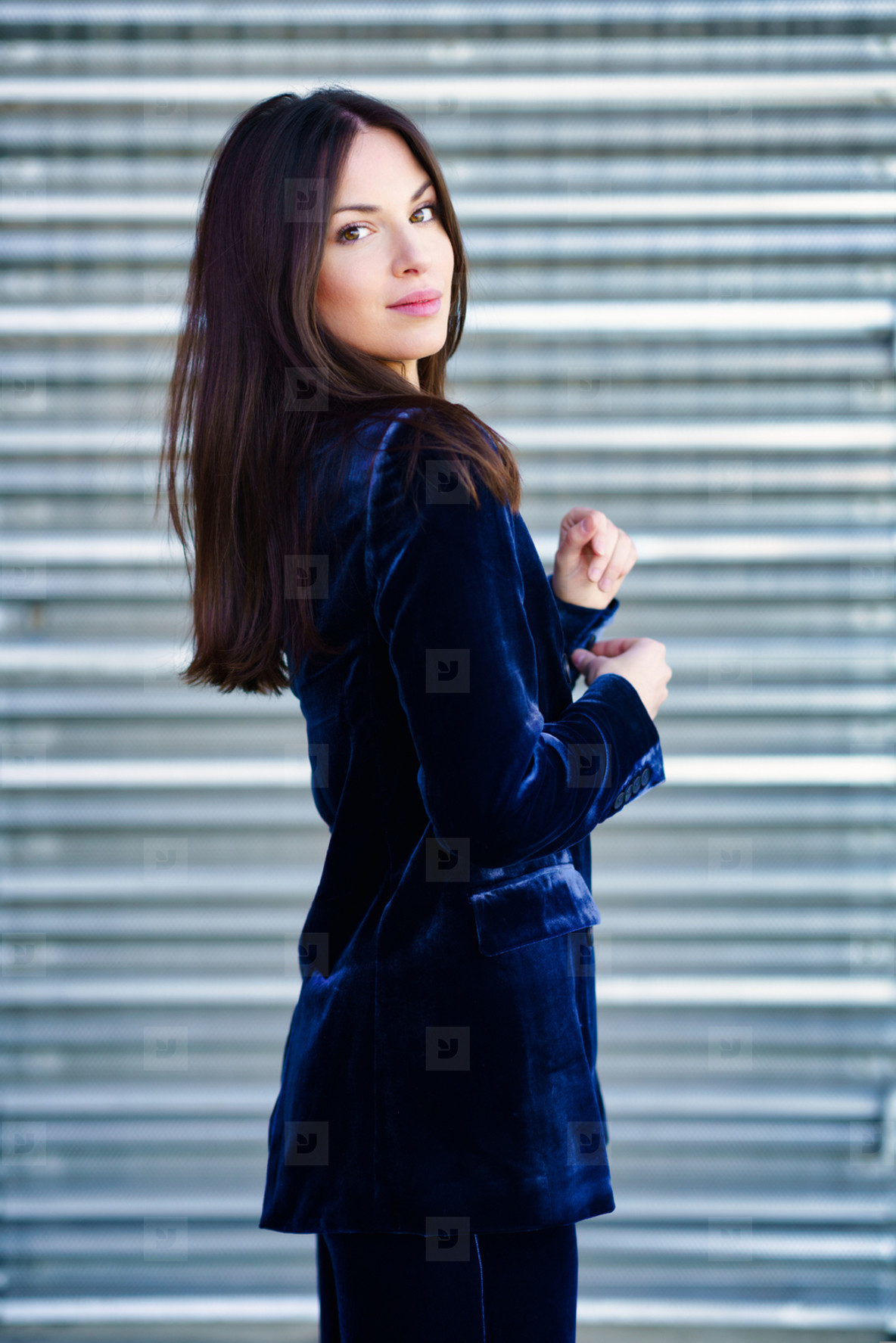 Woman wearing blue suit posing near a modern metal building