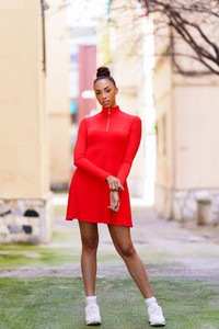 Young mixed woman in red dress posing on a street with colorful walls