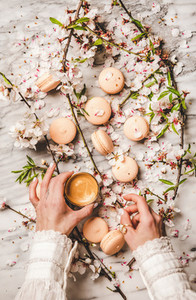 Womans hands holding fresh coffee and macaron cookies