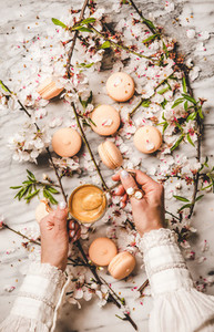Womans hands holding espresso coffee over macaron cookies and flowers