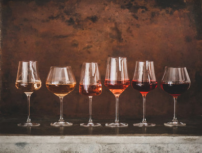 Different shades of Rose wine in glasses over brown background