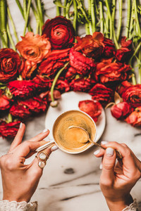 Womans hand holding cup of coffee over table with flowers